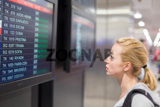 Passenger looking at flight information board.