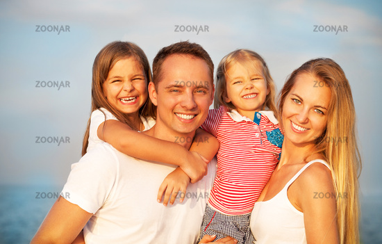 Happy young family with two children outdoors. Summertime