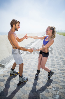 Fit couple rollerblading together on the promenade