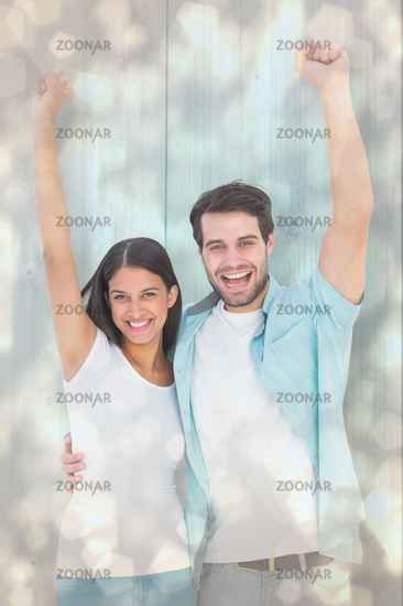 Composite image of happy casual couple cheering together