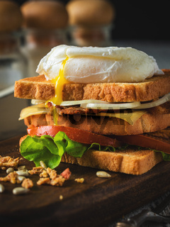 Sandwich with poached egg, tomato, bacon and green salad
