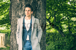Handsome young man leaning against tree