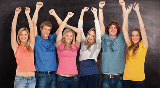 Composite image of a group of people with their hands raised