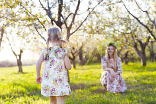 Happy mother and her little daughter in the spring day