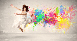 Happy teenager jumping with colorful ink splatter on urban background