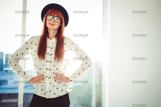Portrait of a smiling hipster woman with hands on hips