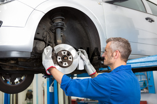 Focused mechanic adjusting the wheel