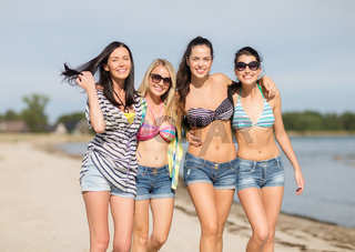 happy teenage girls or young women on beach