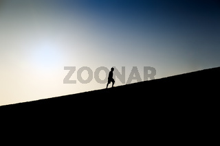 Silhouette of a man climbing a hill