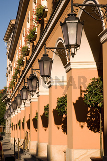 Row of lamps on columns of building