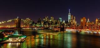 Skyline von Downtown Manhattan mit Brooklyn Bridge und East River in NYC bei Nacht