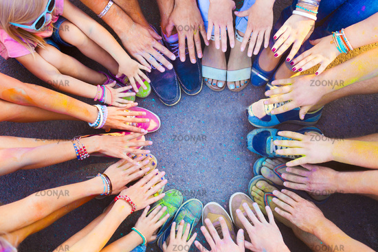 Friends putting their feet and hands together in a sign of unity and teamwork