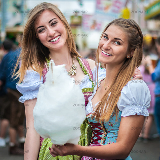 Two young women in Dirndl dress or tracht, smiling with cotton candy floss at the Oktoberfest