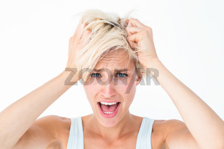 Stressed woman screaming and holding her head
