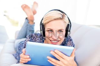 Pretty blonde woman lying on the couch and listening music