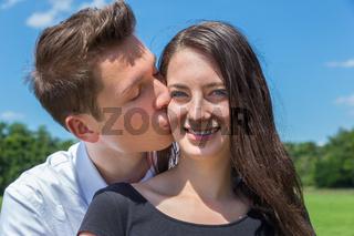 Boyfriend kisses girlfriend on cheek in sunny nature