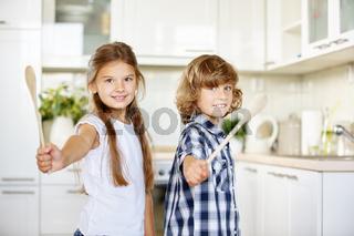 Zwei Kinder haben Spaß und spielen mit Holzlöffeln