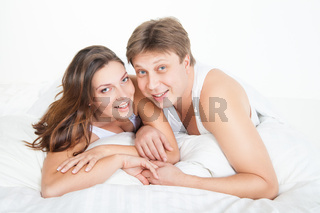 Beautiful young couple relaxing in bed at home