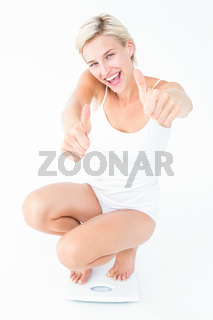 Happy blonde woman crouching on a scales with thumbs up