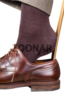 man puts on brown shoe with shoehorn isolated