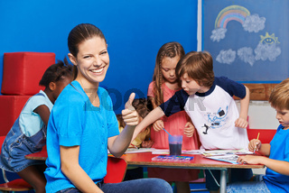 Kindergärtnerin mit Gruppe Kinder hält Daumen hoch