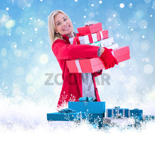 Composite image of festive blonde holding many gifts