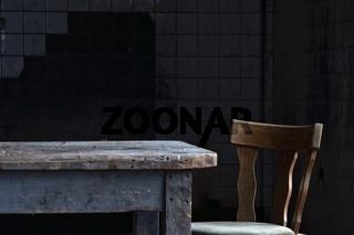 Holztisch mit Stuhl in gekacheltem Raum