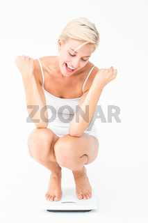 Happy attractive woman crouching on a scales