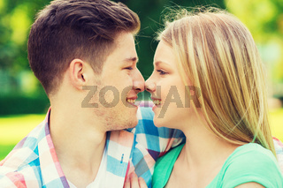 smiling couple touching noses in park