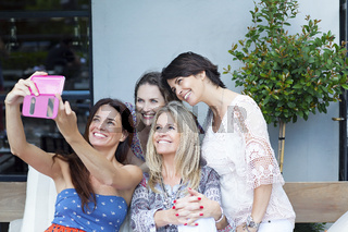 group of friends taking photos with a smartphone in outdoors