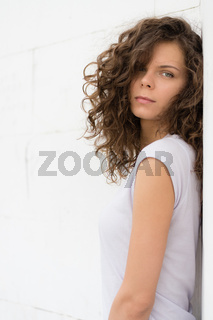 Young attractive woman with curly brown hair on a white background