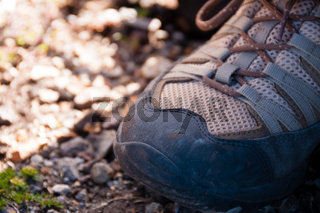 Closeup of a brown beighe trekking Shoe Stepping on Stones