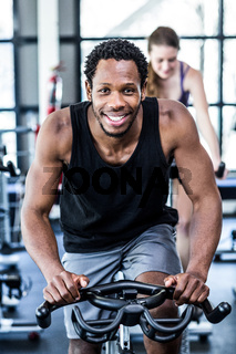 Fit man working out at spinning class