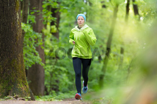 Sporty young female runner in the forest.