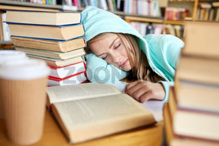 student or woman with books sleeping in library