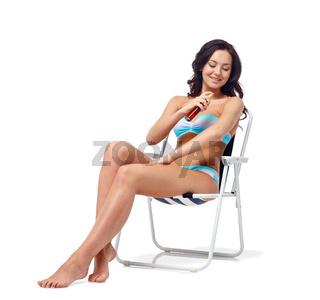 happy woman sunbathing and applying sunscreen