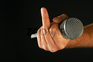 Hand with microphone and fuck off finger on black