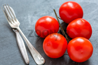 Red tomatoes on a branch, fork and knife.