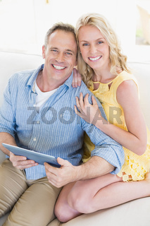 Happy couple using tablet on the sofa