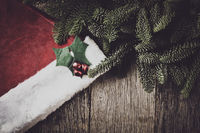 Pine Tree Branches and Santa Hat on Rustic Wood Background