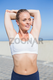 Fit blonde warming up on the pier