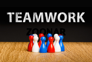 Concept for teamwork in business with white chalk text. Red white blue pawn figures and black background on oak.