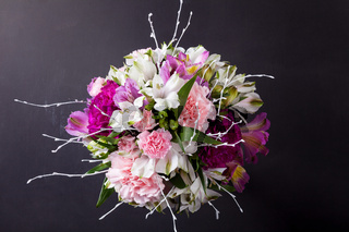 Pink bouquet from gillyflowers and alstroemeria on blackboard, top view