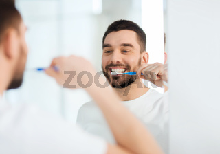 man with toothbrush cleaning teeth at bathroom