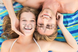 smiling couple lying on a towel looking at camera