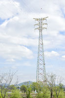 power transmission tower in the field with cloudy sky