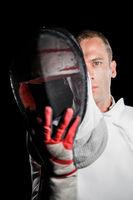 Close-up of swordsman holding fencing mask