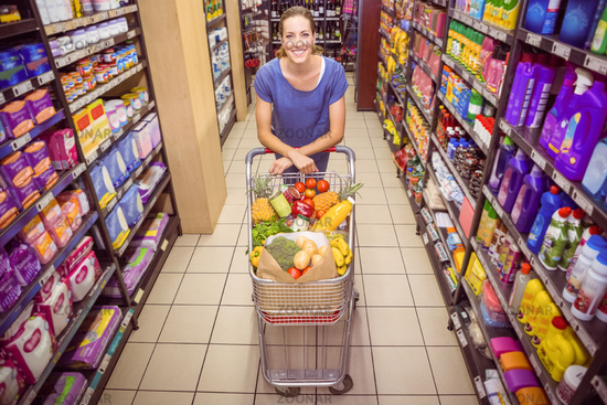 Pretty woman pushing trolley in aisle