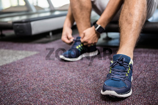 Lower section of man sitting on treadmill and tying the shoelace