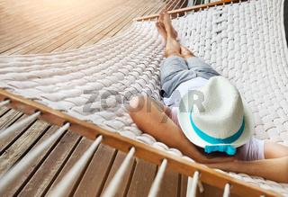 Man in hat in a hammock on a summer day